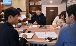 大学前に店を構え、企業と学生をつなぐ「知るカフェ」の交流会。企業の採用担当者(右手前)に質問を重ねる学生たち=西宮市上甲東園3