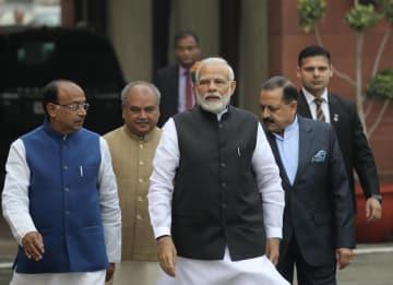 11日、インド・ニューデリーで、報道陣の取材対応に向かうモディ首相(中央)(AP=共同)