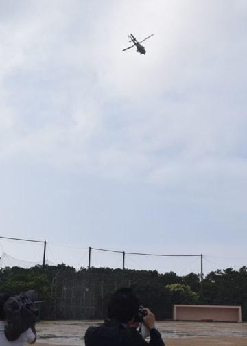 普天間第二小学校の上空周辺を飛行する米軍ヘリ=11日、宜野湾市新城の同小