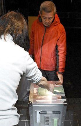 玉東町稲佐地区に計画されているサテライト開設の賛否を書いた投票用紙を投票箱に入れる住民(手前)=玉東町
