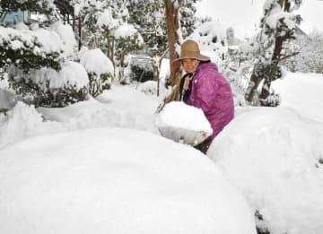 白く覆われた自宅周辺の雪かきに励む新里律子さん=12日午前10時12分、雫石町上野