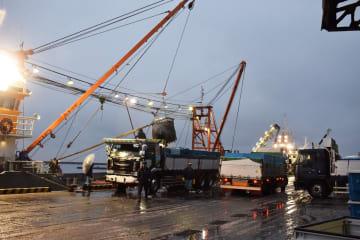 12月中旬になっても異例の大漁が続く八戸港。うっすらと雪が積もる中で水揚げ作業が行われ、トラックがひっきりなしに行き交った=12日午前6時半ごろ、八戸市第1魚市場