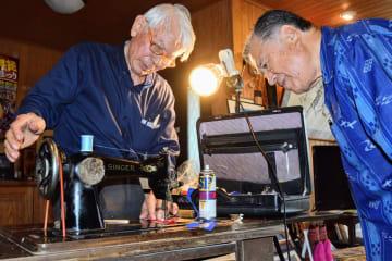 中屋総合ミシン店の棚原弘明さん(左)による修理を終えて、再びミシンが動き出したことを喜ぶ上原政英さん=うるま市高江洲の自宅