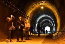 明治のトンネルに積み重ねられた、れんがの多さと時間の重みを確かめる参加者ら=神戸市兵庫区、湊川隧道