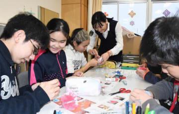 弘前署員と一緒に万引撲滅を願ってマスコットを作成する児童たち