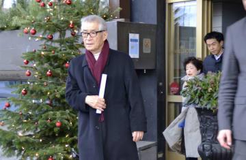 帰国のため、滞在先のホテルを出発する本庶佑・京都大特別教授。右奥は妻の滋子さん=13日、ストックホルム(共同)