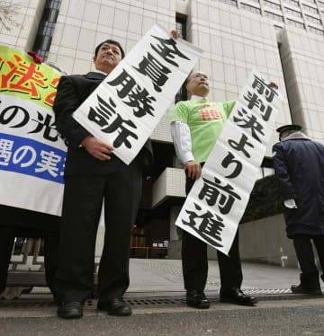 待遇格差是正を求めた訴訟の控訴審判決で、垂れ幕を掲げる原告の宇田川朝史さん(左)と浅川喜義さん=13日午後、東京高裁前