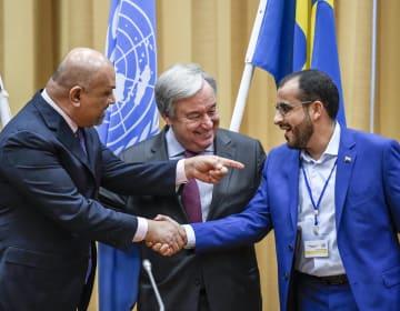 13日、ストックホルムの近郊で握手するイエメンの武装組織「フーシ派」の代表(右)と暫定政権のヤマニ外相(左)。中央は国連のグテレス事務総長(AP=共同)