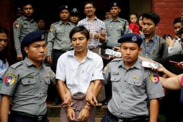 ミャンマーのヤンゴンの裁判所を出る、ロイター通信の記者2人(前後列の中央)=8月20日(ロイター=共同)