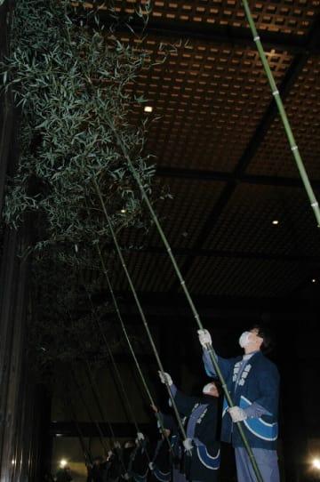 約10メートルのササ竹を使い、夜明け前から大本堂のすす払いが行われた=13日、成田山新勝寺