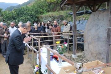 千々石ミゲル夫妻の墓所と推定される墓碑に手を合わせる浅田さん=諫早市多良見町