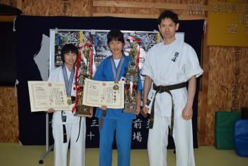 空道の第2回世界ジュニア選手権大会で初出場初優勝を果たした(左から)相内春花さん、神舞優さん、五十嵐祐司代表