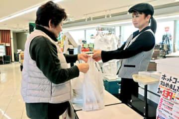 プラスチック製のレジ袋を受け取る買い物客。使用禁止が条例化されれば姿を消すことになる(亀岡市内の小売店)
