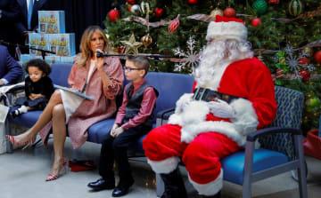 子どもの医療施設を訪れ、サンタを見ながらクリスマスの本を読むメラニア米大統領夫人=13日、ワシントン(ロイター=共同)