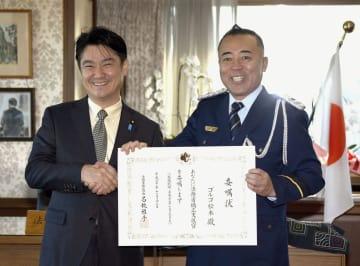 山下法相(左)と矯正支援官の委嘱状を手にするゴルゴ松本さん=14日午前、法務省
