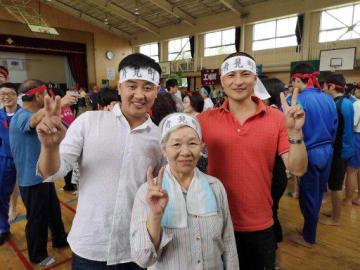江陽地区の住民と中国人労働者(手前の男性2人)らが交流を深めた町内運動会=9月、江陽小学校(北日本造船提供)