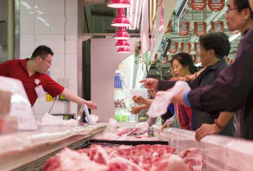 中国山西省太原の食料品売り場で豚肉を買い求める人たち=7月(共同)