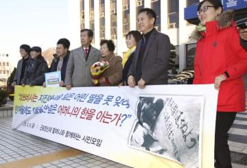 14日、韓国の光州地裁前で勝訴判決に喜ぶ原告の李敬子さん(右から4人目)ら(共同)