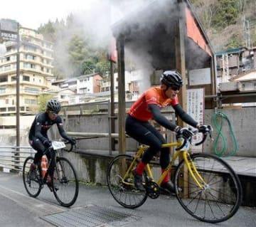 湯煙が立ちのぼる杖立温泉街を自転車で駆け抜ける参加者=小国町