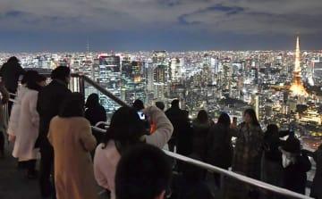六本木ヒルズの屋上で開かれた観察会で「ふたご座流星群」の出現を待つ人たち=14日夜、東京都港区