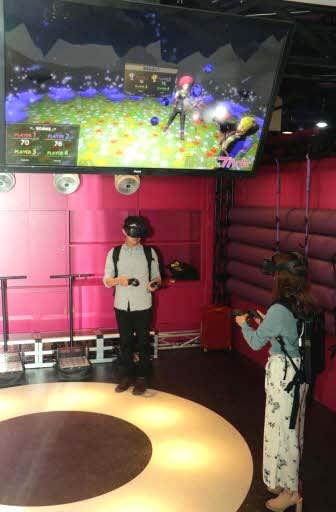 ゴーグルを着用し、VRのゲームを楽しむ人たち(広島市中区のVREX)