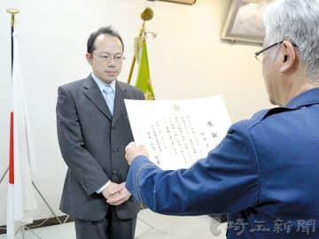 小倉悦男署長(右)から感謝状を受け取る新聞配達員の柳田享さん=朝霞署