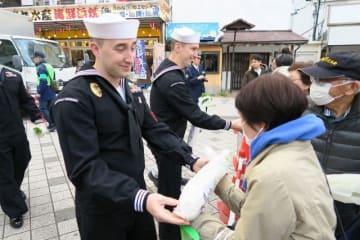 ダイコンを配る米軍人=京急線横須賀中央駅前