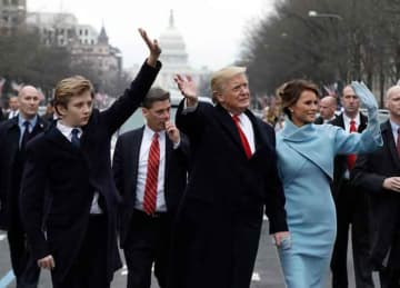 WASHINGTON, DC - JANUARY 20: U.S. President Donald Trump waves to supporters as he walks the parade route with first lady Melania Trump and son Barron Trump after being sworn in at the 58th Presidential Inauguration January 20, 2017 in...