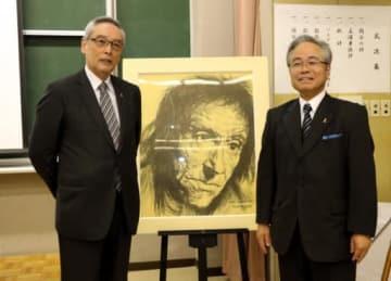 ペスタロッチーの肖像画の前で喜ぶ和田さん(右)と舞鶴学園の桑原施設長