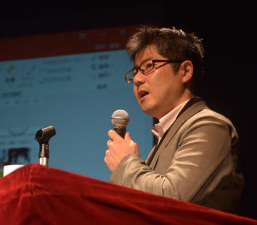 講演する田中成幸さん=ひたちなか市文化会館