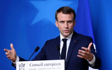14日、ブリュッセルで記者会見するフランスのマクロン大統領(ゲッティ=共同)