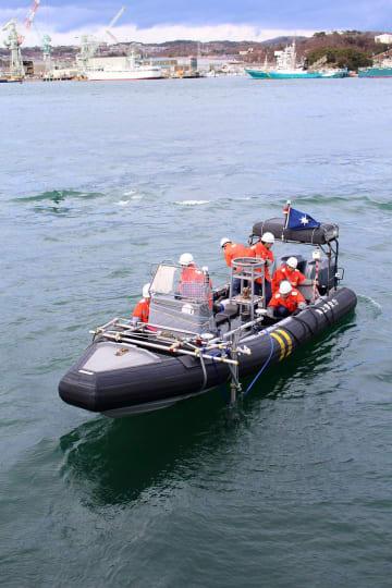ヘリで輸送した小型マルチビーム測深機をゴムボート前方に設置し、海底の障害物の場所を調べる職員