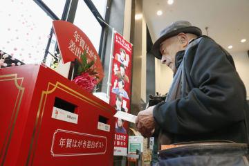 年賀状の配達受け付けが始まり、東京中央郵便局の特設ポストに投函する男性=15日午前、東京・丸の内