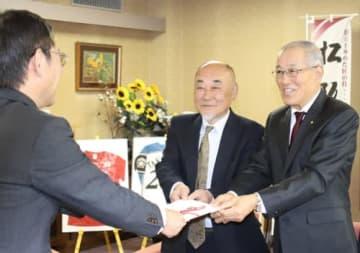 【目録を竹上市長(左)に渡す宇野会長(右)と角谷副会長(中央)=松阪市役所で】