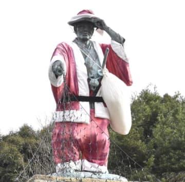 【サンタクロースの衣装に着替えた河村瑞賢の銅像=南伊勢町東宮で】