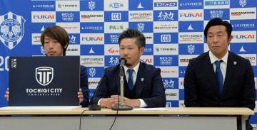 新チーム名と新エンブレムを発表する大栗社長(中央)ら=栃木市役所