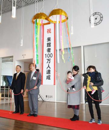 来館者100万人を記念し、くす玉を割る浜畑あきさん(右から2人目)と湊有加子さん(右)ら