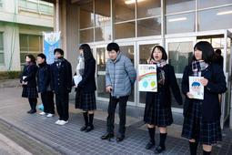 「193募金」と書かれたポスターや箱を手に、山本さん(右から3人目)と募金を呼び掛ける生徒=明石商業高校