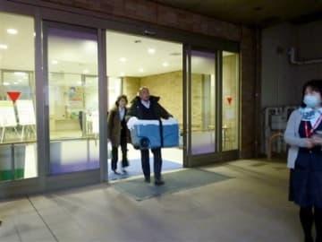 摘出された臓器を収めたケースを運ぶ移植関係者=14日午前7時半ごろ、熊本市東区の熊本赤十字病院(同病院提供)
