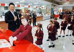 並んで年賀状を投かんする園児。関本賢太郎さん(左端)が見守った=15日午前、神戸市中央区栄町通6、神戸中央郵便局