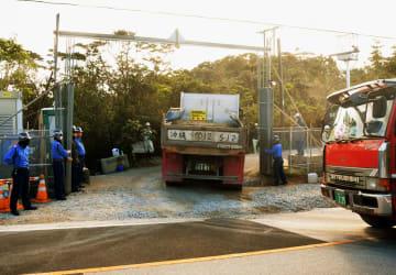 砂利を積んだ工事車両が次々と米軍北部訓練場内に入っていく=14日午前9時すぎ、東村高江