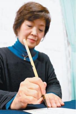 「ぬくもりが伝われば」。一文字一文字に心を込めて年賀状を書く東敬子さん=大分市泉町