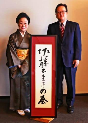 沖縄タイムス社の武富和彦社長から記念品を贈られた佐藤太圭子さん(左)=14日、同社