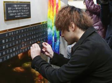 「慰霊と復興のモニュメント」に銘板を付け加える幸田拓哉さん=15日午後、神戸市