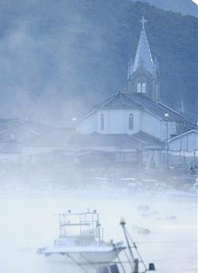 蒸気霧に覆われ、幻想的な雰囲気となった崎津集落=15日午前7時すぎ、天草市河浦町
