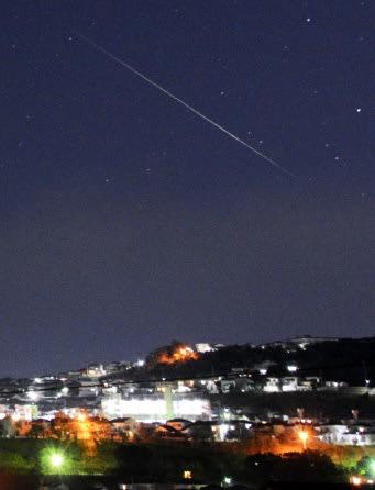 市街地の上空に長く光跡を残すふたご座流星群の流星=鹿児島市下伊敷3丁目