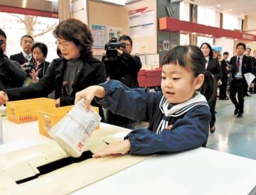 特設ポストに年賀状を入れる園児=15日午前9時ごろ、仙台中央郵便局