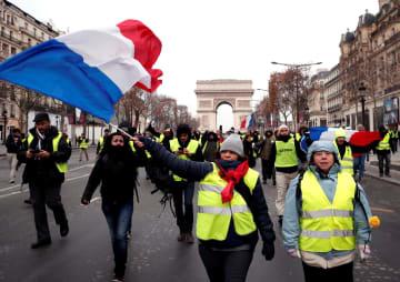 15日、パリのシャンゼリゼ通りでフランス国旗を振る黄色いベスト運動の参加者(ロイター=共同)