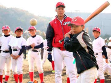 山口投手(奥)の前でバッティングを披露する児童