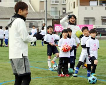 子どもたちのシュート練習を笑顔で見守る佐藤選手(右から3人目)と森崎和さん(手前左)